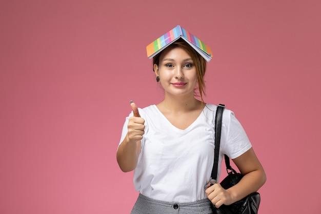 Widok z przodu młoda studentka w białej koszulce i szarych spodniach uśmiechnięta na różowym tle lekcje dla studentów uczelni
