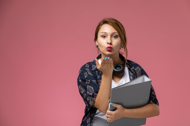 Widok z przodu młoda studentka w białej koszulce i szarych spodniach wysyłająca pocałunki na różowym tle lekcje dla studentów uczelni