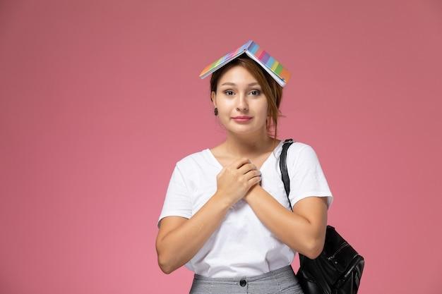 Widok z przodu młoda studentka w białej koszulce i szarych spodniach z zeszytem na głowie na różowym tle lekcje dla studentów uczelni