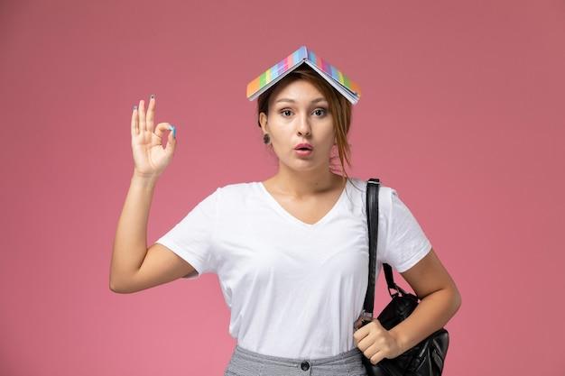 Widok z przodu młoda studentka w białej koszulce i szarych spodniach z zeszytem na głowie na różowym tle lekcji studiów uniwersyteckich