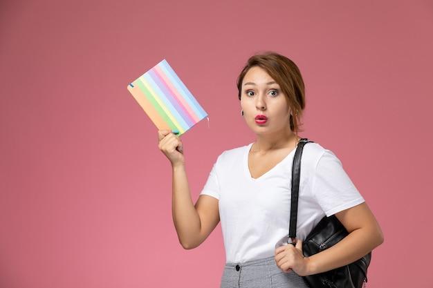Widok z przodu młoda studentka w białej koszulce i szarych spodniach z zeszytem w dłoniach na różowym tle lekcje dla studentów uczelni