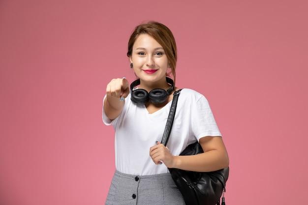 Widok z przodu młoda studentka w białej koszulce i szarych spodniach ze słuchawkami uśmiechnięta na różowym tle lekcje studentów uczelni