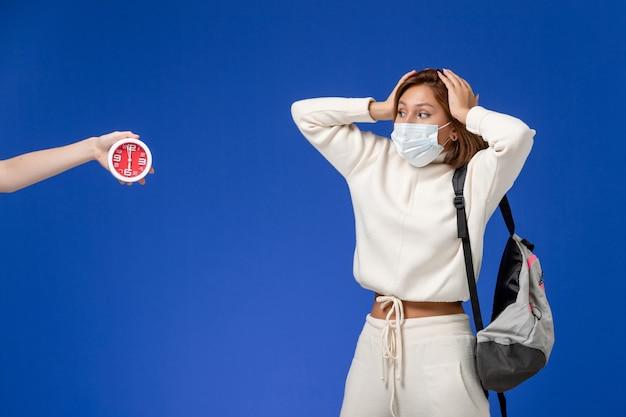 Widok z przodu młoda studentka w białej koszulce na sobie maskę i torbę na niebieskiej ścianie