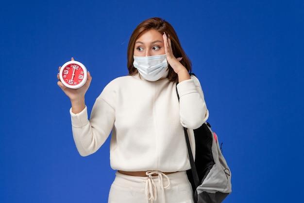 Widok z przodu młoda studentka w białej koszulce na sobie maskę i trzyma zegar na niebieskiej ścianie