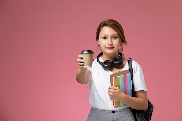 Widok z przodu młoda studentka w białej koszulce z torbą i słuchawkami pozuje i uśmiecha się trzymając kawę na różowym tle lekcja uniwersytecka książka do nauki