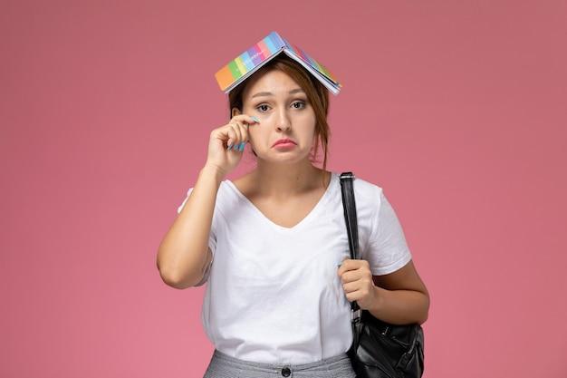 Widok z przodu młoda studentka w białej koszulce z zeszytem i smutnym wyrazem na różowym tle lekcja uniwersytecka książka do nauki