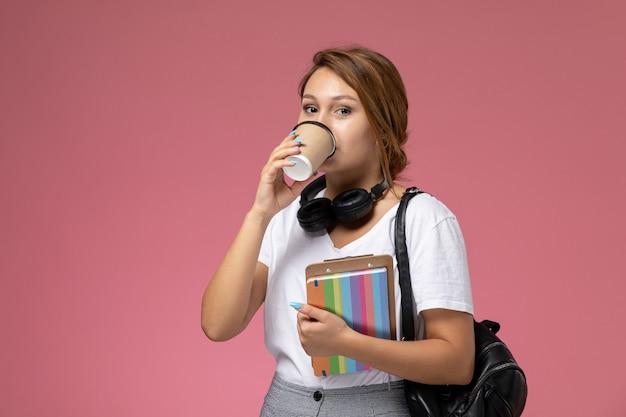 Widok z przodu młoda studentka w białej koszulce z zeszytem i torbą pozuje i pije kawę na różowym tle lekcja uniwersytecka książka do nauki