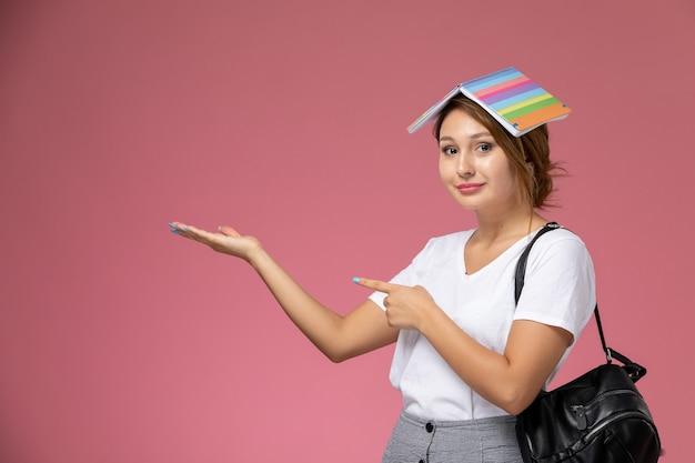 Widok z przodu młoda studentka w białej koszulce z zeszytem i uśmiech na różowym tle lekcja uniwersytecka książka do nauki