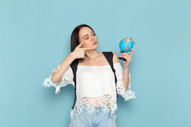 Widok z przodu młoda studentka w białej koszuli, niebieskie dżinsy i czarną torbę trzyma mały glob na niebieskiej przestrzeni uniwersytet żeński