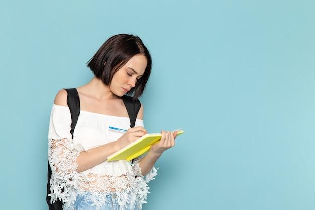 Widok z przodu młoda studentka w białej koszuli, niebieskie dżinsy i czarną torbę zapisywanie notatek na niebieskiej przestrzeni