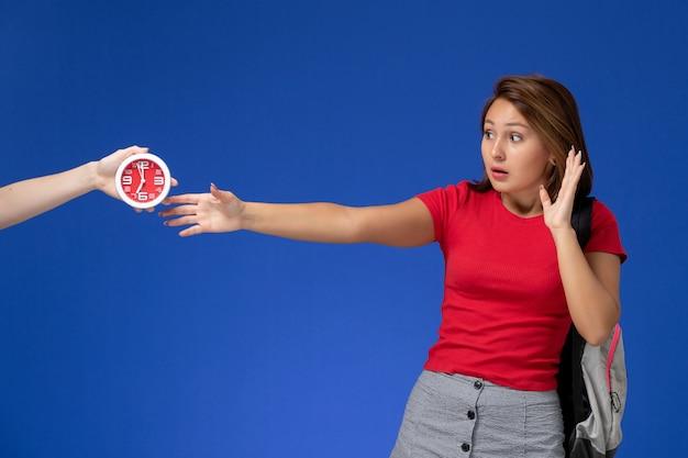 Widok z przodu młoda studentka w czerwonej koszuli na sobie plecak, biorąc zegary na jasnoniebieskim tle.