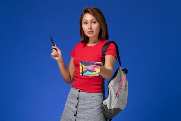 Widok z przodu młoda studentka w czerwonej koszuli na sobie plecak trzyma długopis z zeszytem na jasnoniebieskim tle.