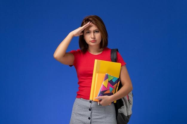 Widok z przodu młoda studentka w czerwonej koszuli na sobie plecak, trzymając pliki i zeszyt na niebieskim tle.