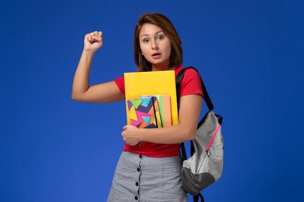 Widok z przodu młoda studentka w czerwonej koszuli na sobie plecak, trzymając zeszyt i pliki na jasnoniebieskim tle.