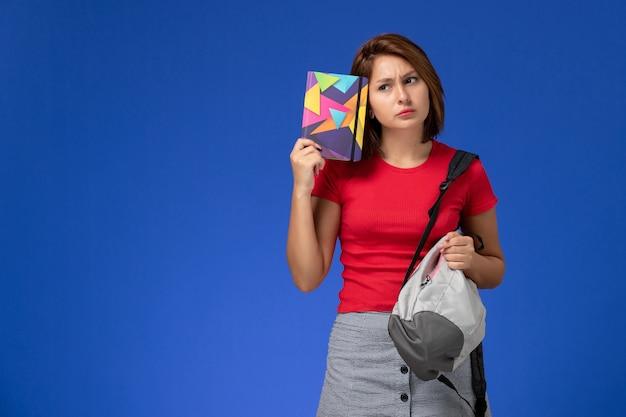Widok z przodu młoda studentka w czerwonej koszuli na sobie plecak trzymając zeszyt myśli na jasnoniebieskim tle.