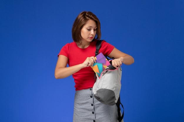 Widok z przodu młoda studentka w czerwonej koszuli na sobie plecak wkładając zeszyt do niego na jasnoniebieskim tle.