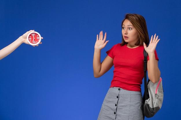 Widok z przodu młoda studentka w czerwonej koszuli ubrana w plecak boi się zegarów na jasnoniebieskim tle.
