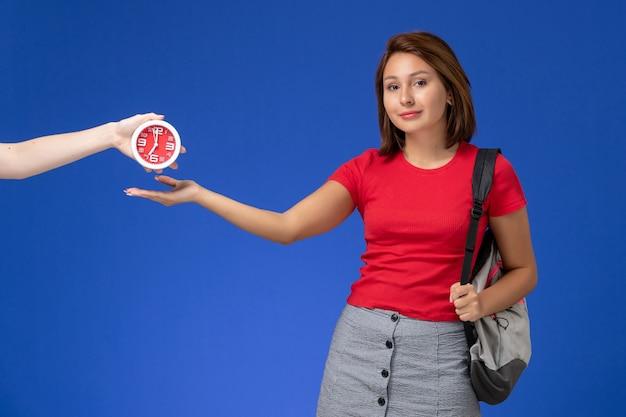 Widok z przodu młoda studentka w czerwonej koszuli ubrana w plecak trzymając zegary uśmiechnięte na jasnoniebieskim tle.