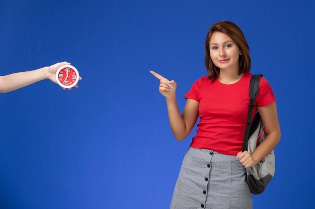 Widok z przodu młoda studentka w czerwonej koszuli ubrana w plecak uśmiechnięta na jasnoniebieskim tle.