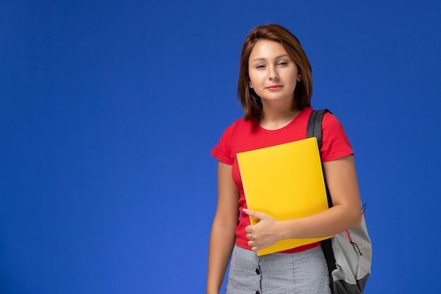 Widok z przodu młoda studentka w czerwonej koszuli z plecakiem, trzymając żółte pliki na jasnoniebieskim tle.