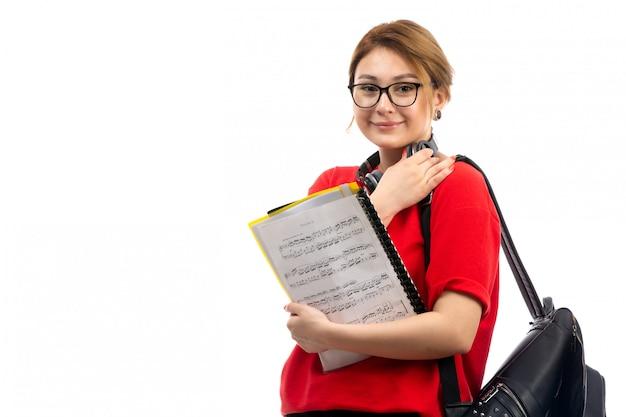 Widok z przodu młoda studentka w czerwonym t-shirt czarne dżinsy w czarnych słuchawkach trzyma notatkę zeszyt uśmiecha się na białym tle