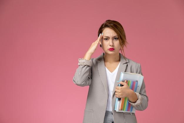 Widok z przodu młoda studentka w szarym płaszczu pozowanie i trzyma zeszyty z bólem głowy na różowym tle lekcji studiów uniwersyteckich