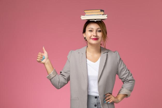 Widok z przodu młoda studentka w szarym płaszczu z książkami na głowie uśmiechnięta na różowym tle lekcje studia uniwersyteckie
