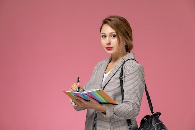 Widok z przodu młoda studentka w szarym płaszczu z zeszytami zapisującymi na lekcjach różowego tła studia uniwersyteckie