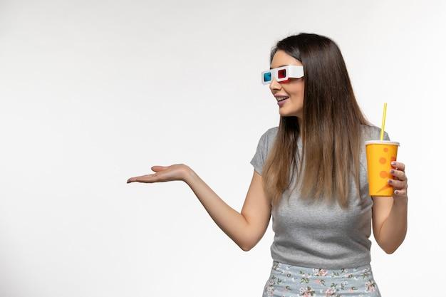 Widok z przodu młode samice sody pitnej w okularach przeciwsłonecznych na jasnobiałej powierzchni