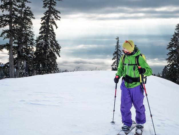 Widok z przodu młodego aktywnego sportowca na nartach lub skitouring splitboard