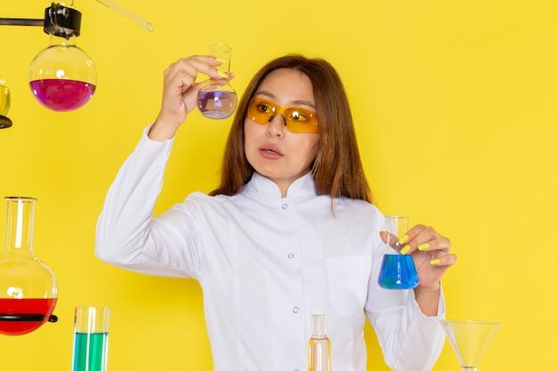 Widok z przodu młodego chemika feman w białym garniturze przed stołem pracującym z roztworami