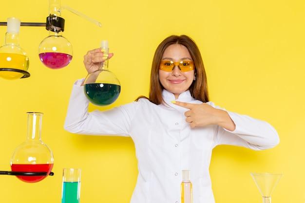 Widok z przodu młodego chemika feman w białym garniturze przed stołem pracy z rozwiązaniami z uśmiechem