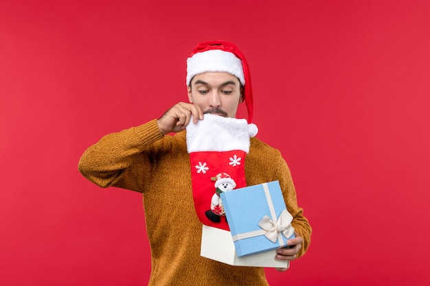 Widok z przodu młodego człowieka, biorąc świąteczne skarpety z pudełka na czerwonej ścianie