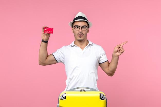 Widok z przodu młodego człowieka emocjonalnie trzymającego kartę bankową na wakacjach na różowej ścianie