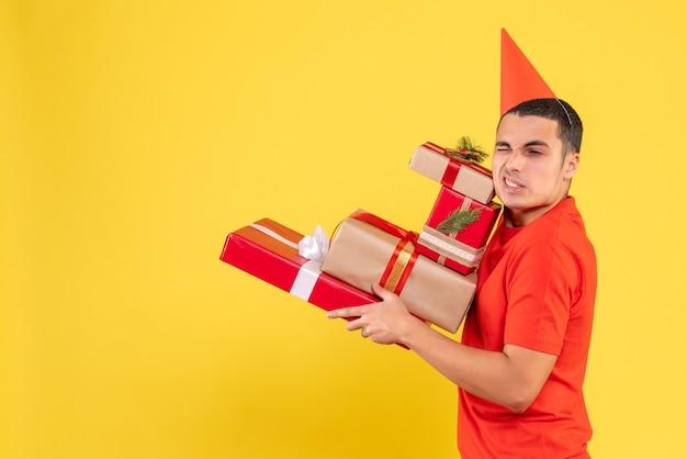 Widok z przodu młodego człowieka niosącego prezenty na żółtej ścianie