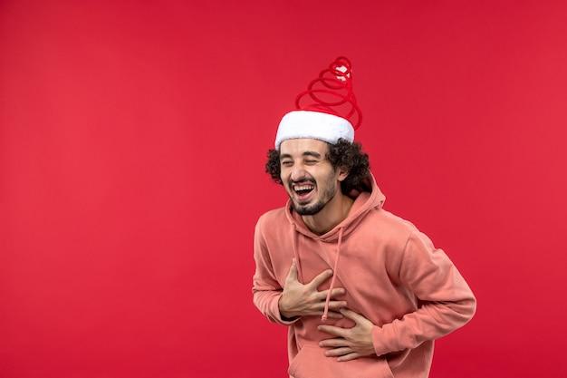 Widok z przodu młodego człowieka śmiejącego się głośno na czerwonej ścianie