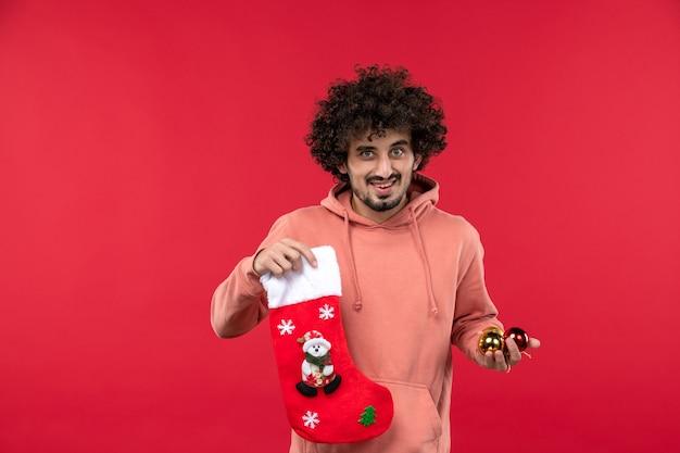 Widok z przodu młodego człowieka uśmiechniętego z zabawkami świątecznymi na czerwonej ścianie