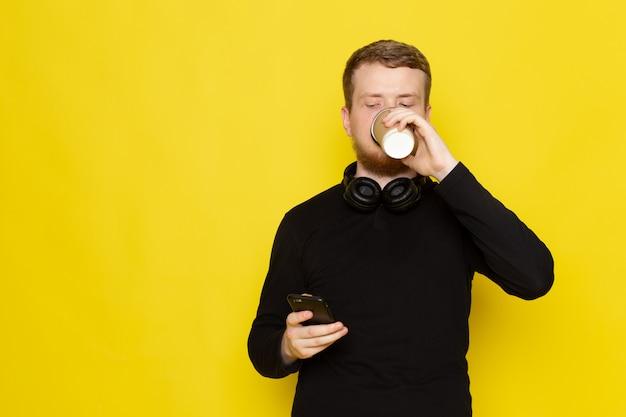 Widok z przodu młodego człowieka w czarnej koszuli przy użyciu telefonu i picia kawy