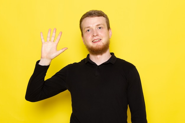 Widok z przodu młodego człowieka w czarnej koszuli z podniesioną ręką i uśmiechem na twarzy