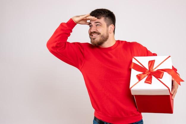 Widok z przodu młodego człowieka w czerwonej koszuli, posiadającego boże narodzenie obecny w pudełku na białej ścianie