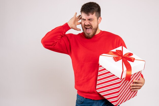 Widok z przodu młodego człowieka w czerwonej koszuli, trzymając prezent gwiazdkowy w pudełku na białej ścianie