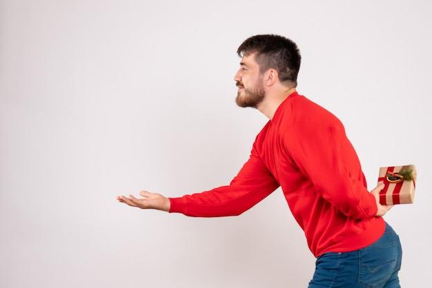Widok z przodu młodego człowieka w czerwonej koszuli, ukrywając prezent gwiazdkowy za plecami na białej ścianie