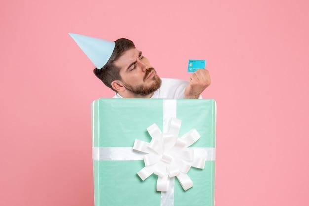 Widok z przodu młodego człowieka wewnątrz obecnego pudełka trzymającego kartę bankową na różowej ścianie