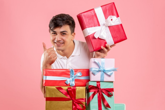 Widok z przodu młodego człowieka wokół prezentów na różowej ścianie