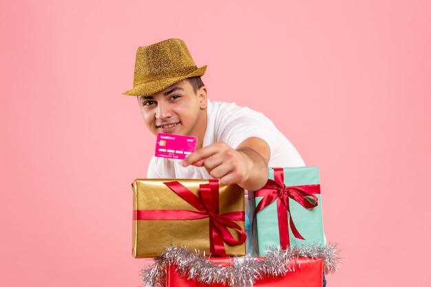 Widok z przodu młodego człowieka wokół prezentów świątecznych, trzymając kartę bankową na różowej ścianie