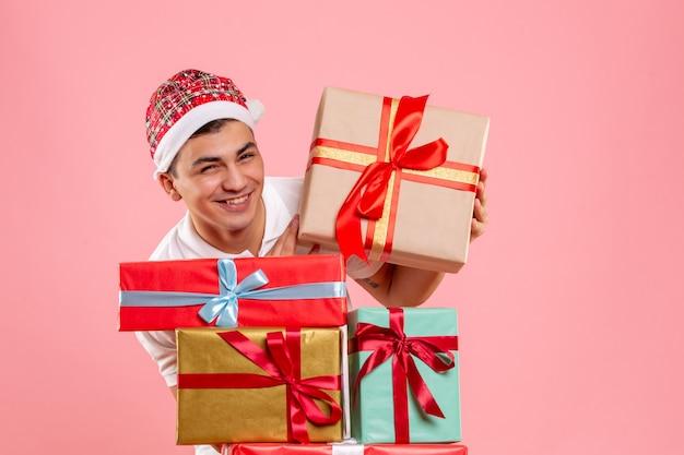 Widok z przodu młodego człowieka wokół różnych prezentów świątecznych na różowej ścianie
