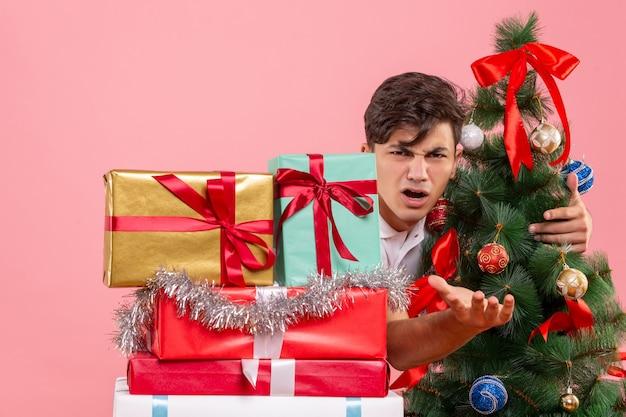 Widok z przodu młodego człowieka wokół świątecznych prezentów i choinki na różowej ścianie