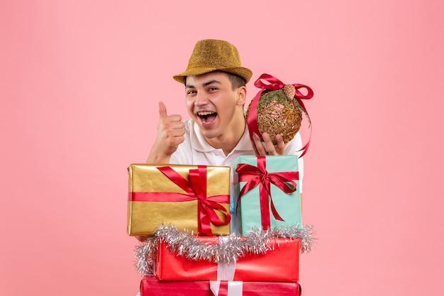 Widok z przodu młodego człowieka wokół świątecznych prezentów na różowej ścianie