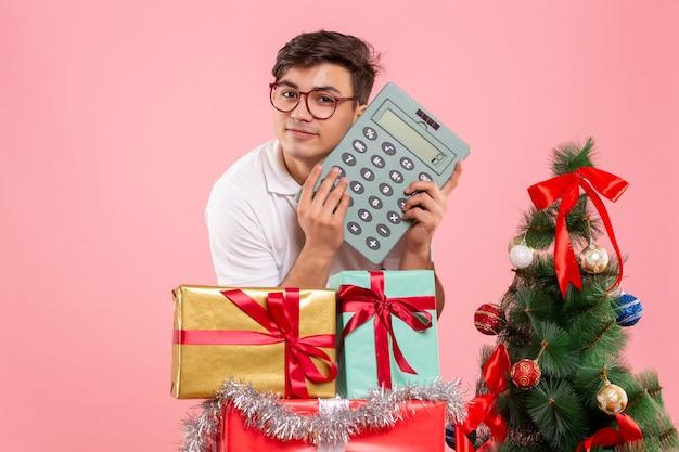 Widok z przodu młodego człowieka wokół świątecznych prezentów trzyma kalkulator na różowej ścianie