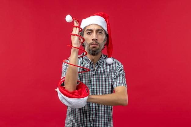 Widok z przodu młodego człowieka z czerwoną czapką zabawki na czerwonej ścianie